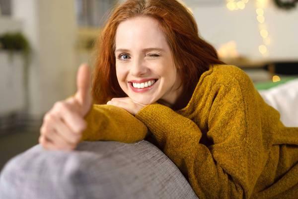 Frau auf Couch mit ausgestreckter Hand und Daumen nach oben